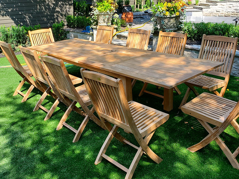 Long rectangular teak dining table surrounded by armless folding chairs