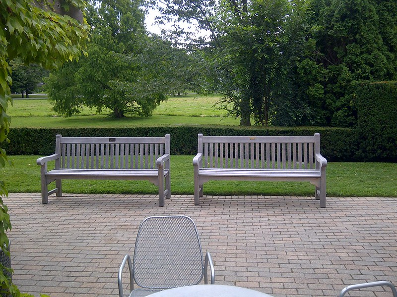 Weathered grey teak benches with straight lines and a slatted back