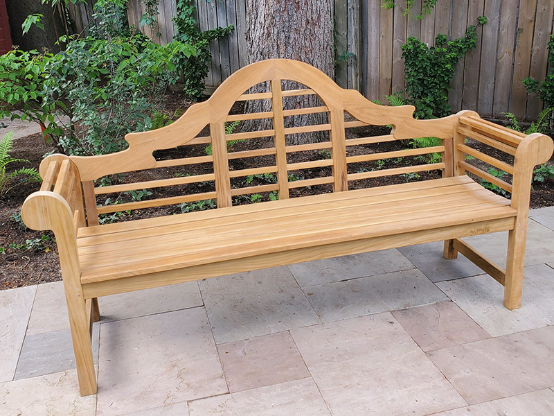 Light teak bench with arms and a slatted scrolled back