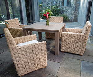 Square tan woven dining chairs with white cushions and square tan table